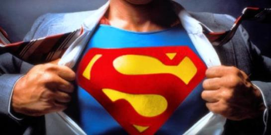 Photo of a man revealing a superman logo on his chest under his shirt