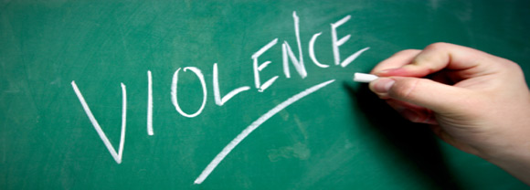 """Photo of a hand writing the word """"violence"""" on a chalkboard"""