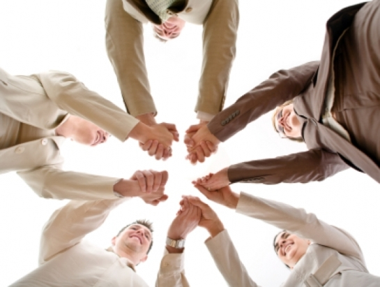 Photo of folks holding hands in a circle
