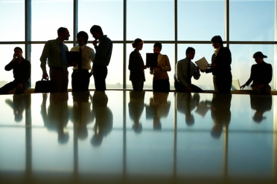 Photo of a room full of business people in silhouette against a window
